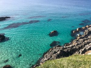 Looking down into crystal clear turquoise water from cliff height.