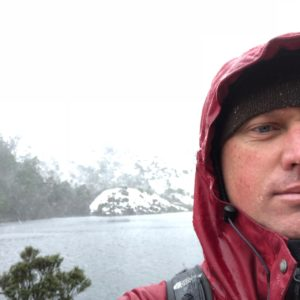 A man with wet cheeks stands in front of a snowy mountain lake wearing a red rain coat hood